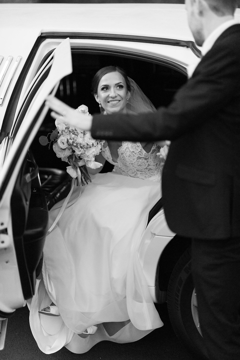 groom opening the door to let the bride out of the limo