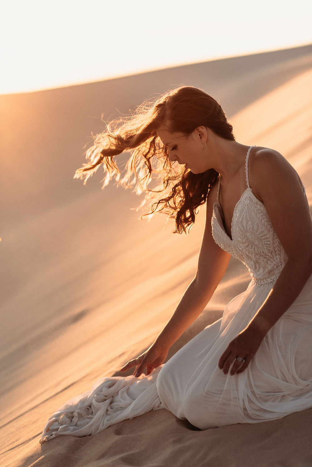bride sits in sand, fussing with her wedding dress. the sun is setting behind her and the golden light illuminates her hair blowing in the wind,