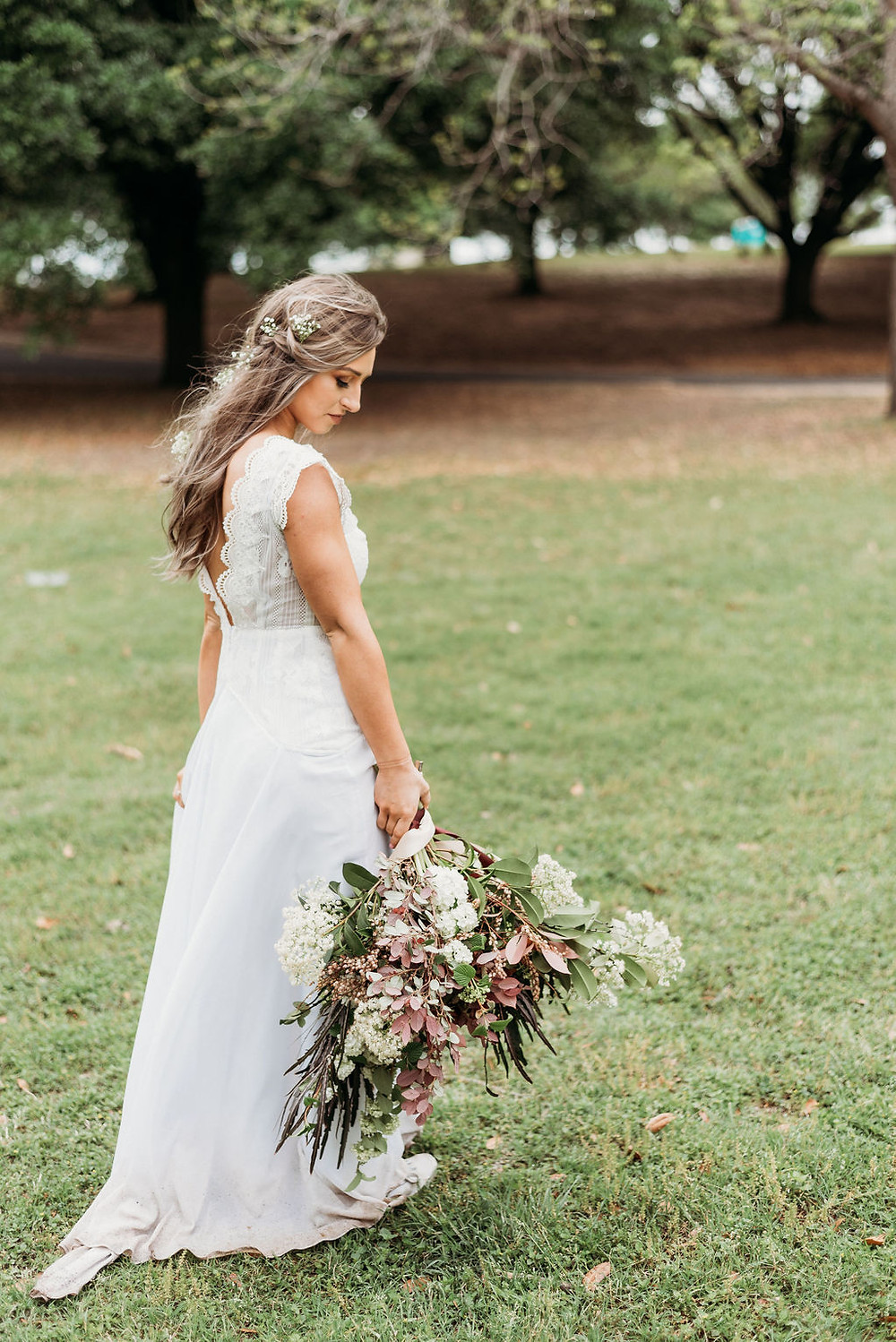 bride looks down at her bridal bouquet from wow factor floral during their austin elopement. boho bride is wearing a boho wedding dress and her wedding hair is styled relaxed and down with baby's breath in her hair