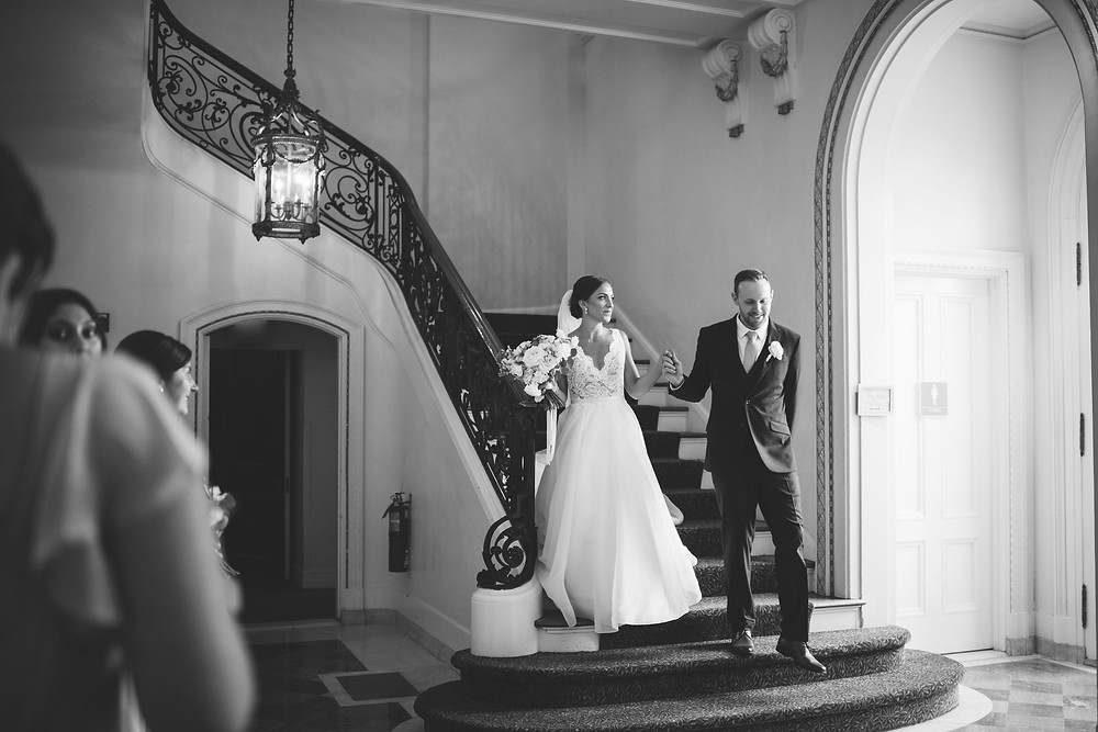 couple walking down the grand staircase at Tupper Manor to rejoin their guests after photos