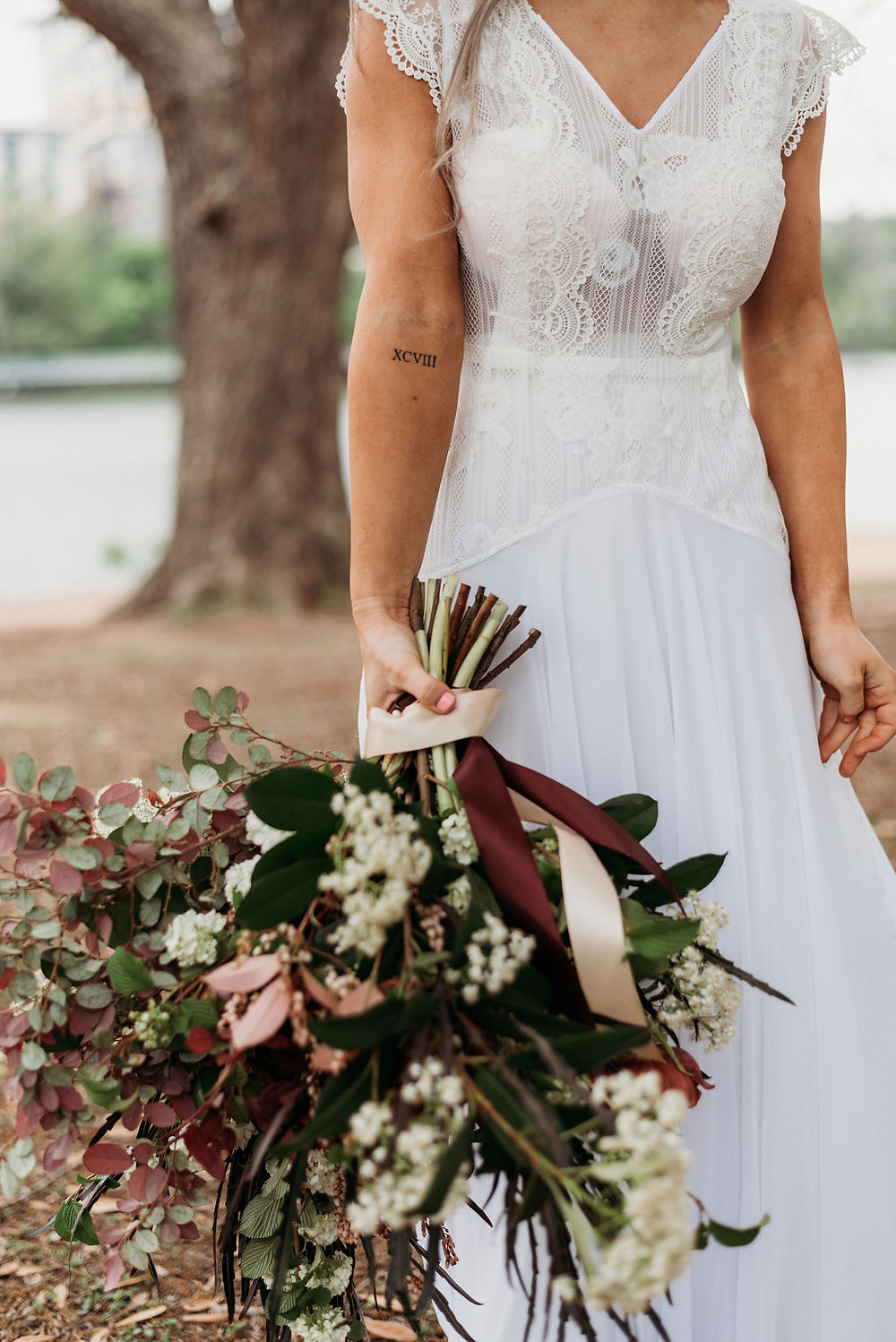 bridal portrait. bride holds her bouquet down to her side so that you can see her forearm tattoo. the photo is cropped so that you cannot see her face- only her shoulders to he knees
