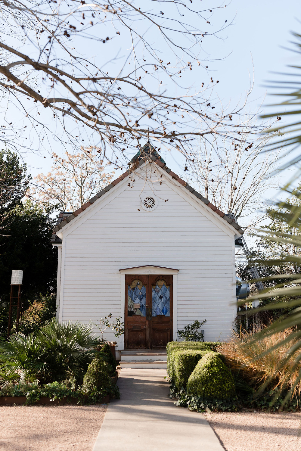 small white building that resembles a chapel. it is the kitchen at barr mansion. there are two wooden doors in the middle of the building that have stained glass windows. There are beautiful bushes and trees surrounding the perimeter