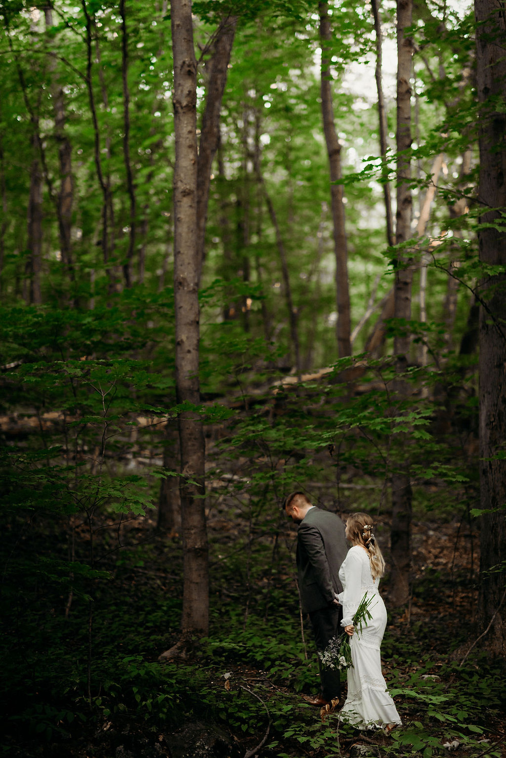 bride and groom holding hands walking through the woods at middlesex fells reserevation