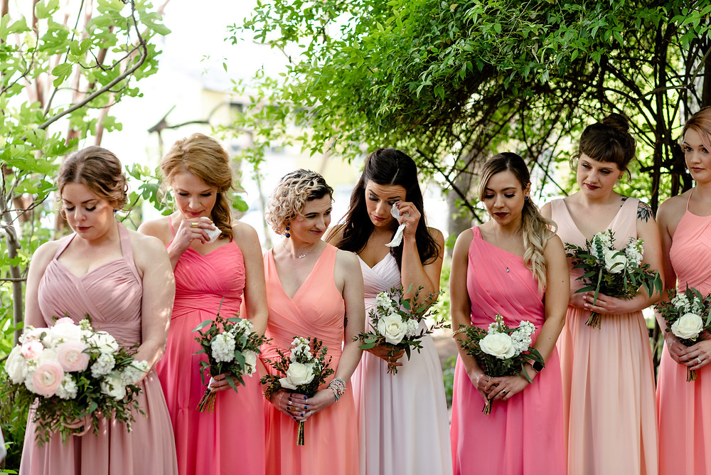 bridesmaids crying as bride walks down the aisle