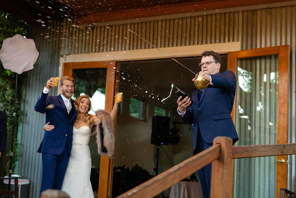 best man sabring a bottle of champagne with a sword at a wedding