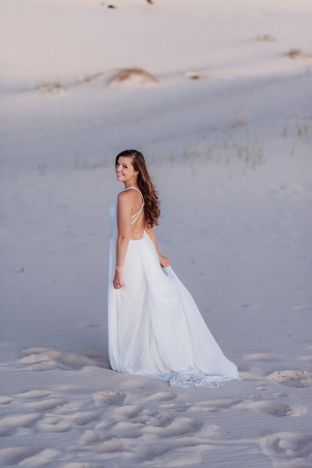 photo of a girl in a wedding dress standing on sand. her back is turned away from the camera to show the detail on the back of the dress but she is looking back over her shoulder at the camera smiling