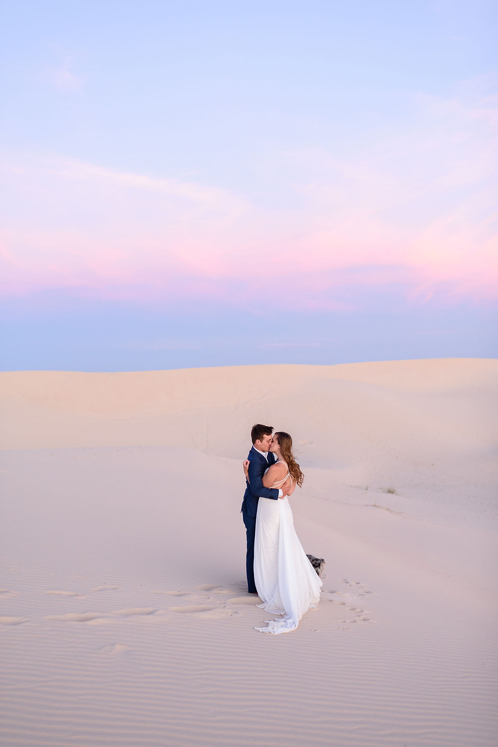 couple embraces in the middle of the sand. there is a cotton candy sky behind them as the sun sets over monahans sandhills