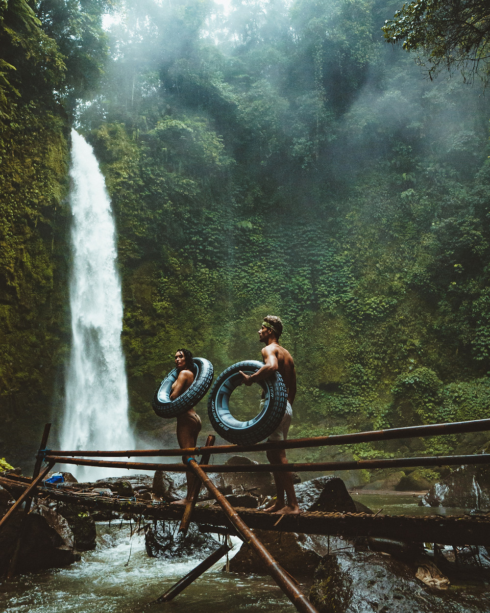 Couple on an exotic honeymoon carrying inner tubes walking towards a waterfall.