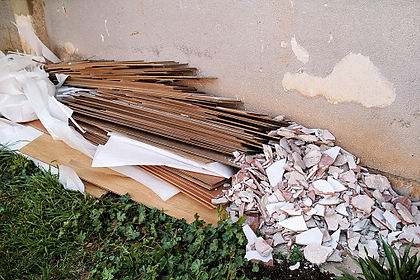 A pile of old floorboards and broken tile laying against a wall