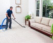 Man vacuuming carpet floor