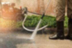 A person pressure washing a driveway