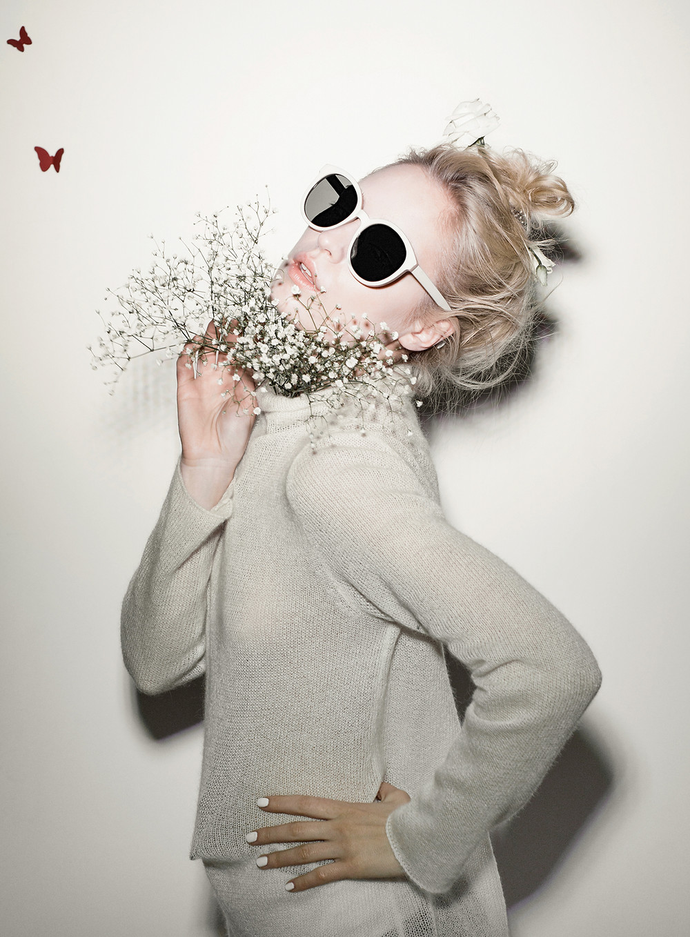 A confident woman. A woman with sunglasses. A woman holding some flowers around her neck. A woman wearing a cream jumper. A woman with blonde hair. Image with butterflies in the backdrop. A young and confident woman.