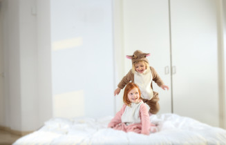 Two girls in animal onesies jumping and playing on a bed