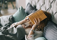 woman-covering-face-with-book-on-bed-152