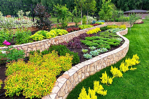 Stone masonry landscape retaining wall with bushes and trees