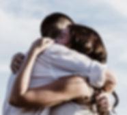 Um casal se abraçando emocionados