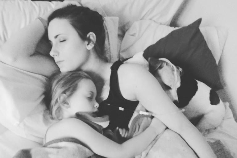 A black and white photo of Bella asleep in bed, on one side is a small child, and on the other a little terrier type dog. Both are also asleep.