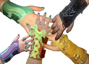 5 White hands, each wearing a wrist brace.  Each brace is a different color with different embellishments. One is purple, one green, one black, one yellow, and one multi-colored. They're embellished with beads, ribbon and fringe.