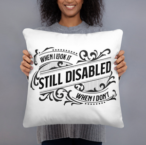 "A black female presenting person in a gray sweater holding out a white square pillow with a black flourish design that reads, ""when I look it, STILL DISABLED, when I don't."""