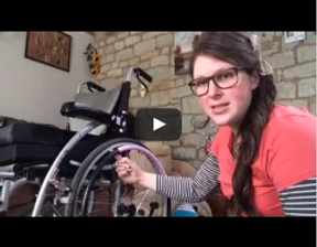 A video still of a brown-haired white woman with glasses, sitting on the floor next to a wheelchair with decorated wheels.