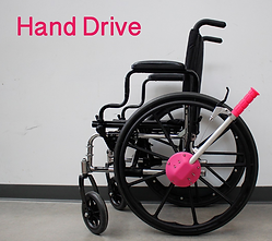 A black wheelchair with an attachment at the center of the wheel.  The attachment is silver with a pink handle and extends in a bar towards the back of the chair.