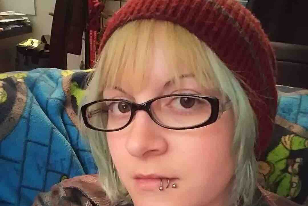 A close up photo of a white person's face.  they have medium length dyed hair covered by a dark red knit cap.  In addition to 2 piercings at the bottom right of their lip, they have dark oval glasses and are looking at the camera.