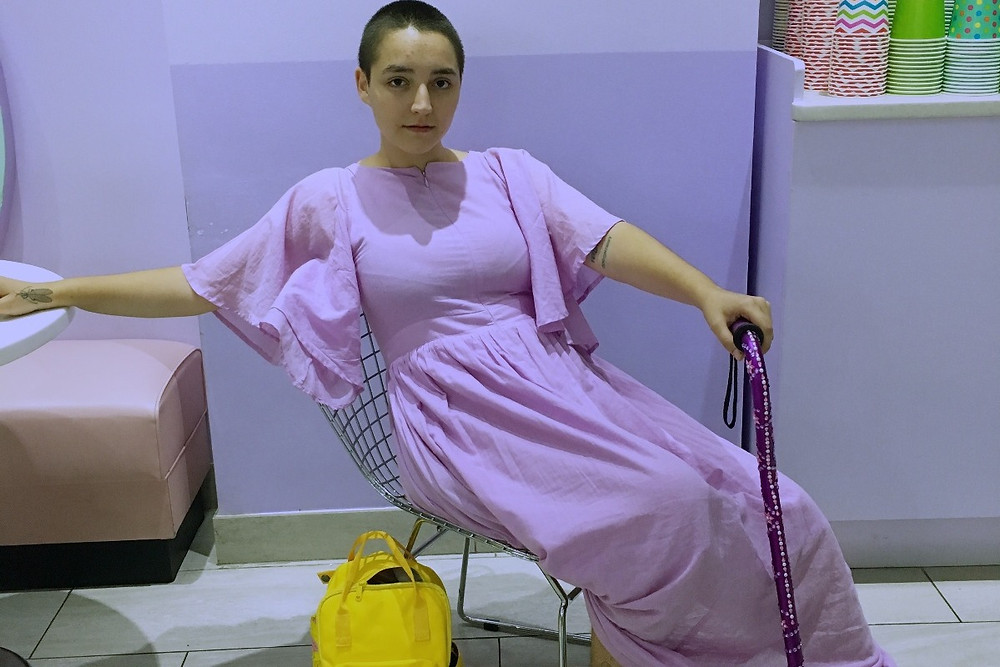 A photo of Elce seated in a wire chair.  They're dressed in all purple and holding a sparkling purple cane.