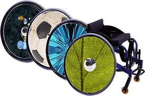 A wheelchair with a spoke guard that looks like a close up photograph of a leaf, with 3 other spoke guards in a blue abstract, as a soccor ball and another featuring a galaxy theme.