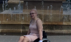 Alexa sits in a manual wheelchair.  She has pink hair and is wearing a pink dress.  She's positioned in front of a fountain.