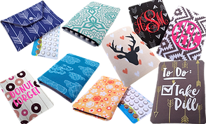 A variety of fabric rectangular pill wallters.  Each is large enough to hold a sheet of pills and are showin in a variety of patterns.