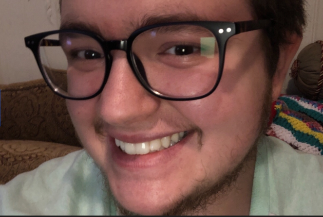 A close-up photo of Chris wearing glasses and smiling at the camera.