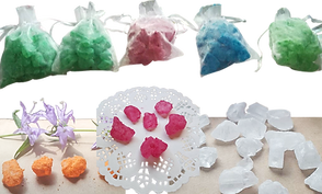 Across the top are 5 drawstring opaque white bags with bath crystals in them, 2 Green, a red, a blue and another green.  Across the bottom are orange, pink, and white bath crystals displayed out of bags.