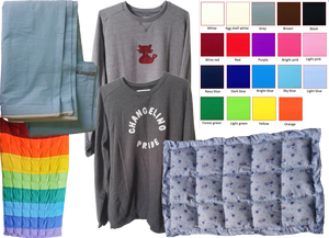 """A color cart with 16 color options, a folded but empty weighted blanket, 2 sweatshirts- one featurin a small red cat with neurdivergent infinity symbol bow-tie, and one reading, """"Changeling Pride,"""" a long rainbow colored weigted blanket, and a blue floral weighted lap blanket."""