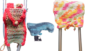 A crutch with a knitted bag attached, a cane head with a knitted cover, and the top of a crutch with a knitted pad.