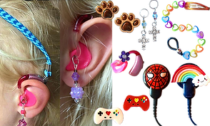 2 ears wearing hearing aids- one has a teal and black band attached and stretched over her head, the other showing a purple bejeweled earring attached to the molded part of the aid. A set of pawprint tube charms, a pair of video came controller charms, a pair of cross hearing aid earrings, a rainbow heart beaded clip that attaches to a barette, and 2 cochlear implant s with charms- one spiderman and one rainbow.  A hearing aid with a small purple flower attached.