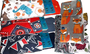 fabric pouches with button over covers that hold 7 day am/pm pill cases.  The covers are in different patterns.  One has cats, another a denim and red design, another nautical, another gray with red foxes in hats and glasses, another in a floral motif, and the last in a black red and white paisley design.