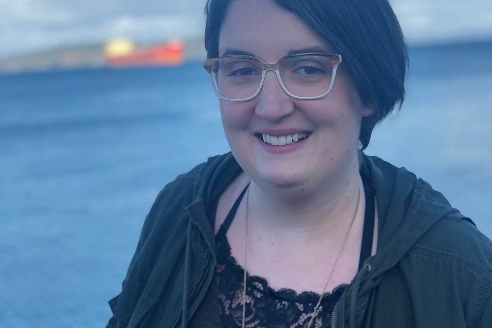 A photo of Alisha. She is looking into the camera and smiling, and has short brown hair and silver glasses.