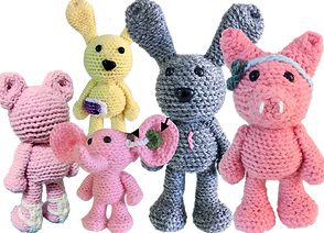 5 Crochted stuffed animals.  A pig with a BAHA device, a pink elephant with a hearing aid, A gray bunny with a surgical scar, a yellow rabbit with a cgm and the back of a pink bear showing afos braces.