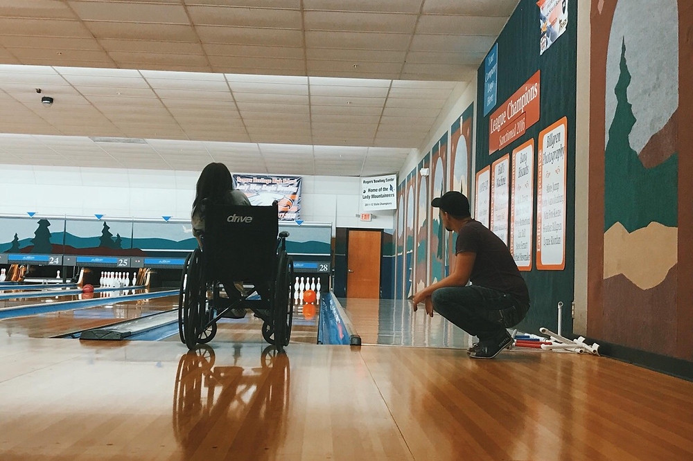 A person in a wheelchair watches a bowling ball roll down a lane towards pins.  Next to them is another person squatting to watch as well.
