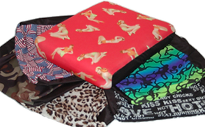 Photo of a stack of various cushion covers including camo, leopard, pinup girls, rainbow and one with words.
