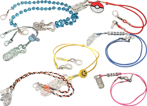 7 cords with clear clips attache for securing hearing aids and cochlear implants. Each has a dfferent charm ad 4 are diffeent solid colors, one is brided in black orange and white, and one s beaded with blue diamond shaped beads.