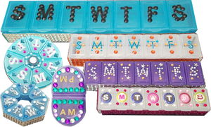 Plastic pill cases with the letters for the days of the week on each compartment and bedazzled with lots of colors.