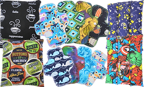 2 square heatable pads, one with white coffee cups on black, and one with a range of brewing labels, 2 rows of 4 different patterned fabric pads and 2 sectioned heatable pads, one with stars on blue and one with marvel characters.