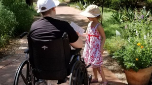 A photo of a person in a black manual wheelchair photographed from the back.  They are wearing a black shirt and a white baseball cap.  Standing beside them is a child in a red and white dress wearing a  tan hat.  They are on a pathway that appears to be going through a garden area.