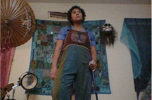 Aster stands above the camera, holding a black cane and looking into the distance.