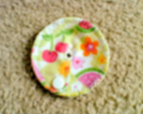 a round hand-made g-tube pad with flowers and cherries on it.