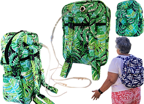 A green tropical leaf patterned backpack shown from different angles.  From the back and side view oxygen cannulae can be seen extending from a grommeted hole at the top of the pack.  A person in a white shirt wears the pack in anothe pattern on their back.