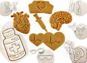 Raw and baked cookies showing different medical related cookie cuters. A pill bottle, anatomical heart and brains, a syringe, spine, ear with hearing aid, glasses and more