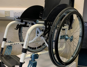 The frame of white and black a kuschall ultra-light manual wheelchair.