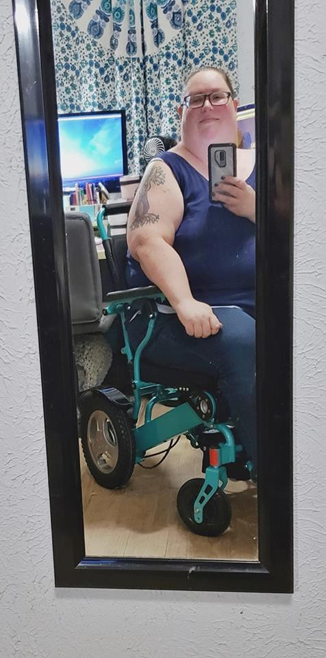 A photo of a fat white woman in a navy blue tanktop sitting in a bright turquoise power chair.  She has an intricate tree tattoo on her arm, and is clearly taking a mirror selfie with her phone.
